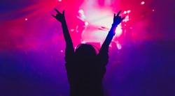 Silhouette of young girl partying on concert in nightclub.Music hall background.Young woman put hands up to music with rock on gesture.Rock & roll concert audience backdrop.Female wave hands in club