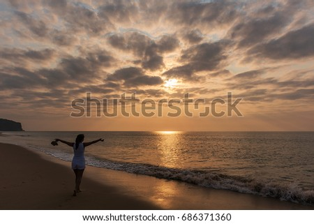 Silhouette of young girl with open arms, with sunset and dramatic sky. #686371360