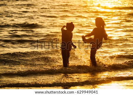 Silhouette of young girls kicking splash water on the beach at sunset. #629949041