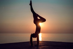 Silhouette of young gymnast standing on hands in a beautiful pose on the beach at sunset. Sun comes up and woman doing exercise on the pier. Professional yoga teacher practicing handstanding outdoors