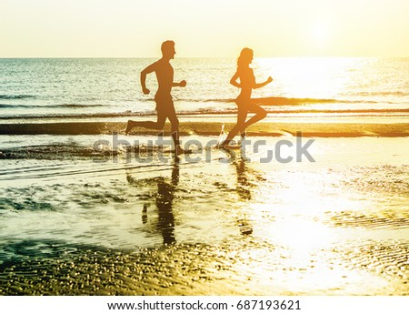 Silhouette of young happy couple running on seashore splashing water with back sun light - Two cheerful lovers having fun on the beach - Love and vacation concept - Soft focus on him - Warm filter #687193621