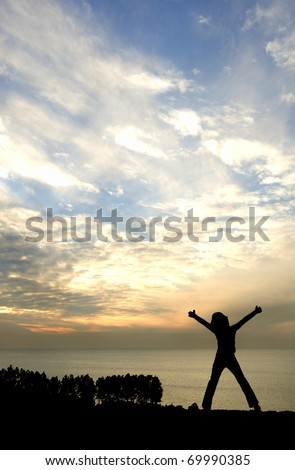Silhouette of young happy girl looking out to sea with arms stretched in victory pose