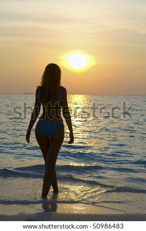 Silhouette of young harmonious woman of going in ocean towards sunset.
