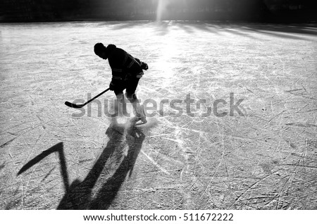 Silhouette of young hockey player making fun on natural ice. Original, sport, winter wallpaper - black and white photo