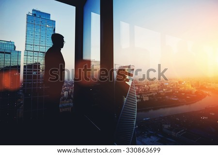 Silhouette of young intelligent man managing director resting after late business meeting while standing near big office window background with copy space for your text message or promotional content