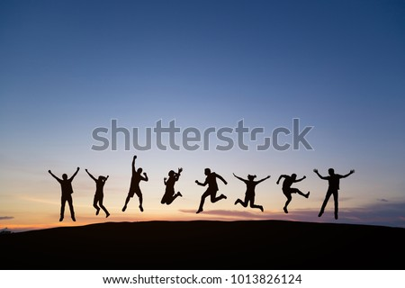 Silhouette of young man and woman jumping to celebrate success on top of hill, sky and sun light background. Business, successful, happy, teamwork and goal concept.