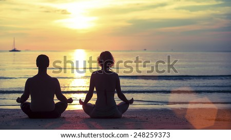 Silhouette of young man and woman practicing yoga in the lotus position on the ocean beach during amazing sunset.
