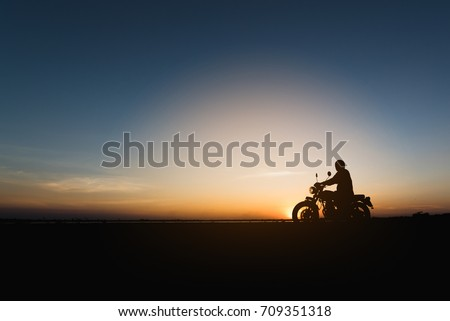 Silhouette of young man biker  and a motorcycle on the road with sunset light background
