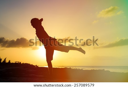 Silhouette of young man doing yoga at sunset beach #257089579