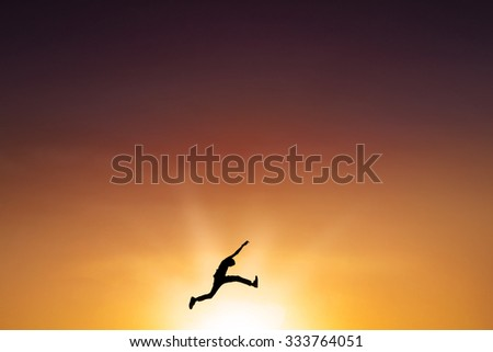 Silhouette of young man enjoy vacation and jumping on the air at sunset time #333764051