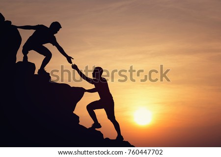Silhouette of young man helping each other hike up a mountain at sunset. Business, teamwork, achievment, success concept. Vintage filter.