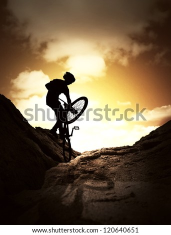 Silhouette  of  young man jumping on the mountain bike