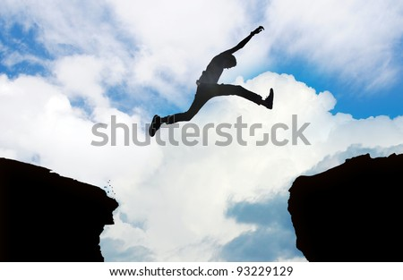 Silhouette of young man jumping over a cliff