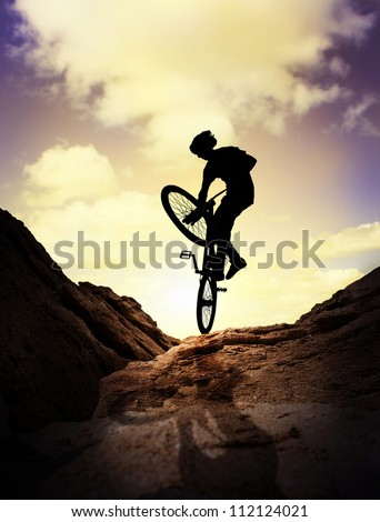 Silhouette  of young man on the mountain bike over purple sunset sky
