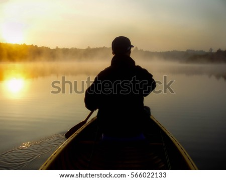 Silhouette of young man paddling a classic wooden canoe at dawn on a calm lake in northern Michigan