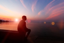 Silhouette of young man sitting on the beach at a twilight time.