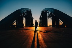 silhouette of young man standing at the bridge in Kiev, Ukraine