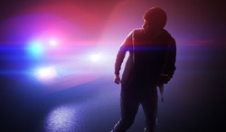 Silhouette of young man - thief escaping from police car at night.