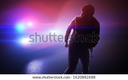 Silhouette of young man - thief escaping from police car at night. Foto stock ©