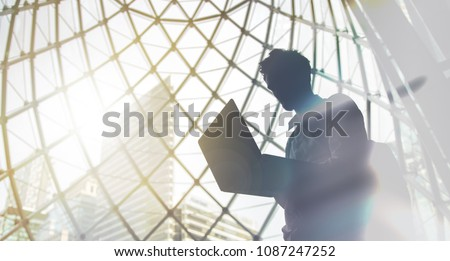 Silhouette of young man with laptop