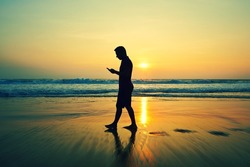 Silhouette of young man with mobile phone on the beach at sunset