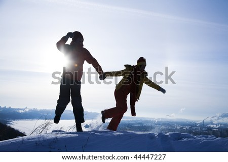 Silhouette of young pair running in winter park