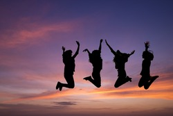 Silhouette of young people jumping together,friend having fun and happy with sunset background.Friendship Day,unity and freedom concept.