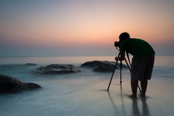 Silhouette of young photographer on the beach.