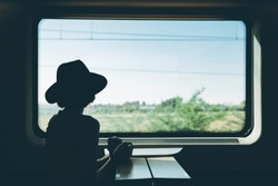 silhouette of  Young pretty woman traveling alone by train, holding a camera and looking at the view through the window. Enjoying travel.