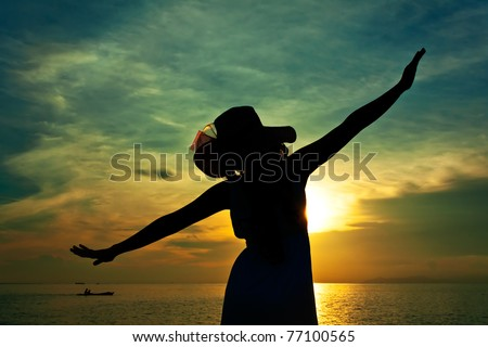 Silhouette of young pretty woman with hat during sunset