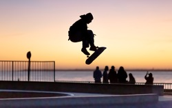 silhouette of young skater jumping on ramp