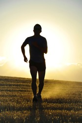 silhouette of young sport man running off road in countryside straw field with strong backlight at summer sunset in a beautiful rural landscape in healthy lifestyle and training concept