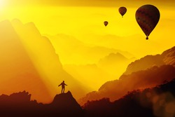Silhouette of young traveler standing on top of mountain with amazing Fantasy sunset with hot air balloons.Travel Lifestyle success concept,adventure active vacation outdoor,happiness freedom emotion.