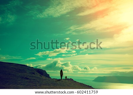 Silhouette of young woman and dog against sea fjord at magical sunset.  Summertime. Twilight time on the beach. Wild nature, seascape. Trendy color. Calm sea. Nordkapp.