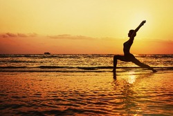 Silhouette of young woman doing yoga on the beach in hero pose