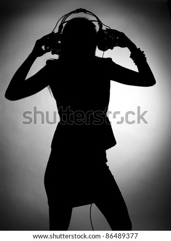 Silhouette of young woman enjoys listening music in headphones. Classic monochrome photography.