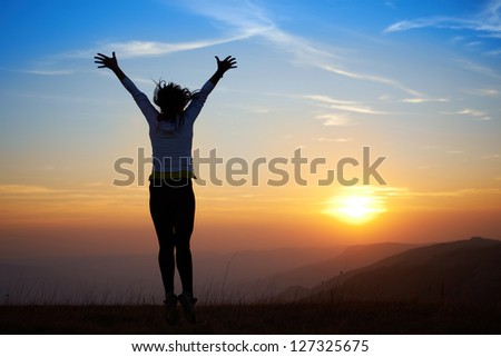 Silhouette of young woman jumping against sunset