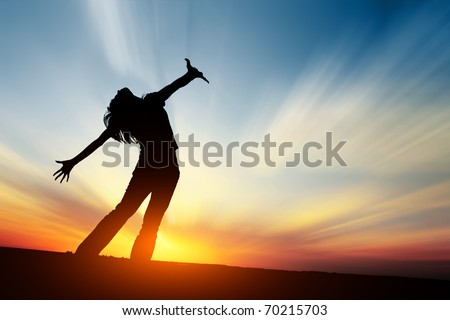 Silhouette of young woman on sunset