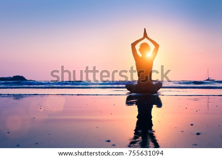 Silhouette of young woman practicing yoga, lotus position, and meditating on the beach