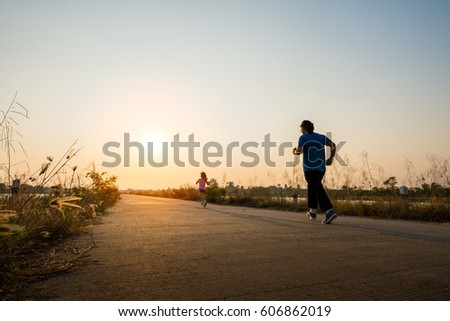 Silhouette of young woman running on road against sunset for exercise #606862019