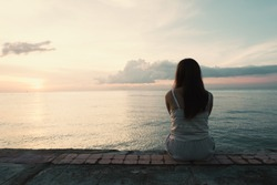 Silhouette of young woman sitting alone on back side outdoor at tropical island beach missing boyfriend and family in summer sunset. Sad and lonely concept in dark and vintage tone.