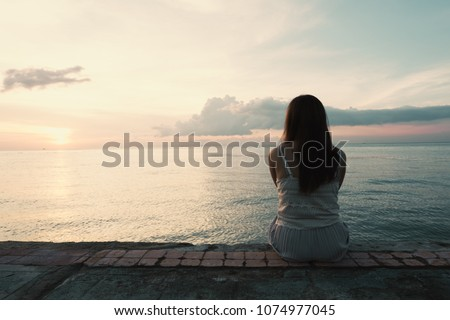 Silhouette of young woman sitting alone on back side outdoor at tropical island beach missing boyfriend and family in summer sunset. Sad and lonely concept in dark and vintage tone. #1074977045