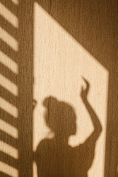 Silhouette of young woman stands with her hand up dancing in sunshine in the morning at home. Contrast window shadows on the wall. Aesthetic shade portrait. Lights and shades. Shade silhouette.