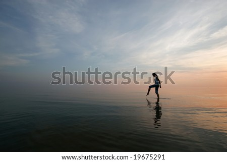 Silhouette of young woman wading in sea at sunset