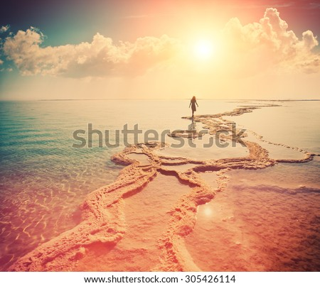 Silhouette of young woman walking on Dead Sea at sunrise. Solitude
