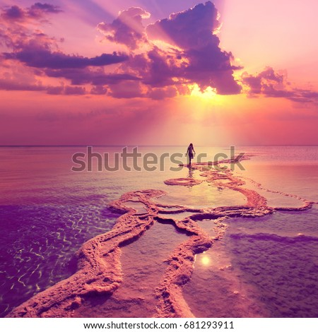 Silhouette of young woman walking on Dead Sea with beautiful sky at pink sunrise