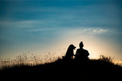Silhouette of young woman with her dog in the sunset outdoor.