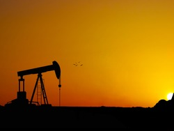 Silhouette oil well beam pump with nice sunset