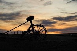 Silhouette Old Haymaking Machine (tractor) on grass field sunset time
