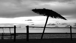 Silhouette or black & white or contrast photo of bamboo hand made fence and bamboo umbrella on the beach